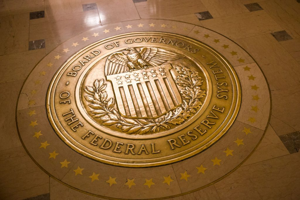 Light reflects off a gold-plated seal inside the Marriner S. Eccles Federal Reserve Board Building in Washington, D.C.