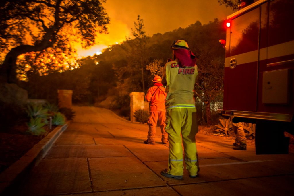 Firefighters watch as the Thomas Fire approaches homes in December 2017, in Montecito, California.