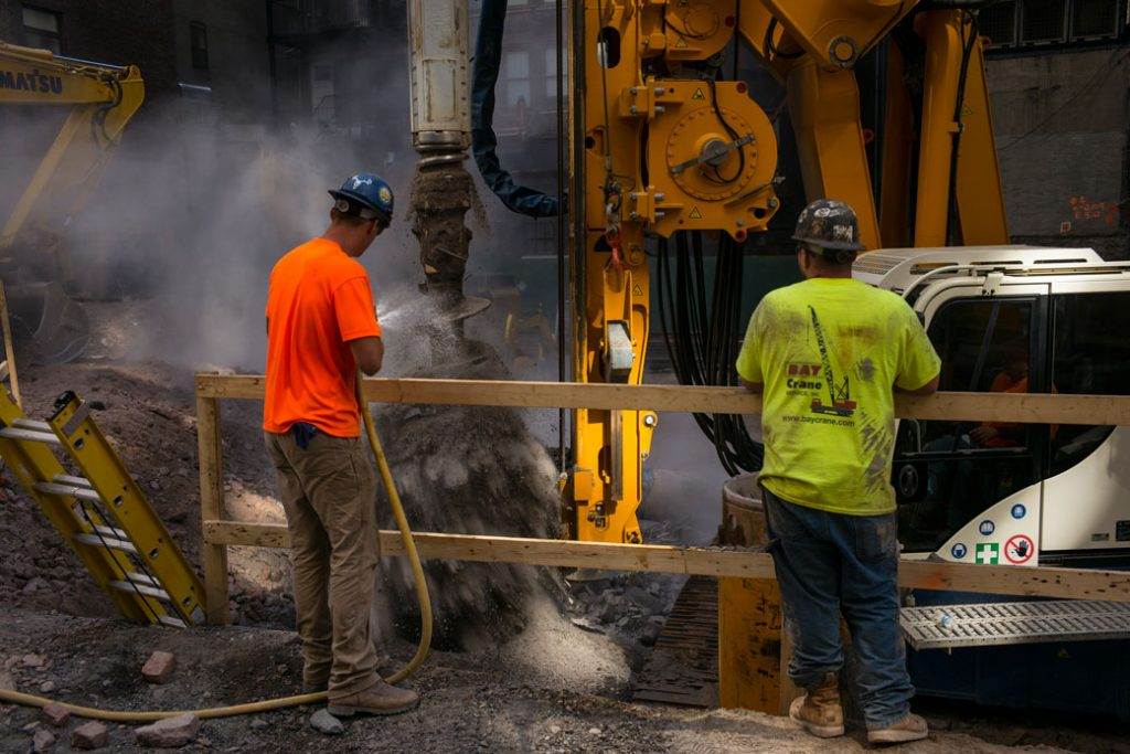 Construction workers clean a rotary drilling auger at a building site in New York City, July 2018.