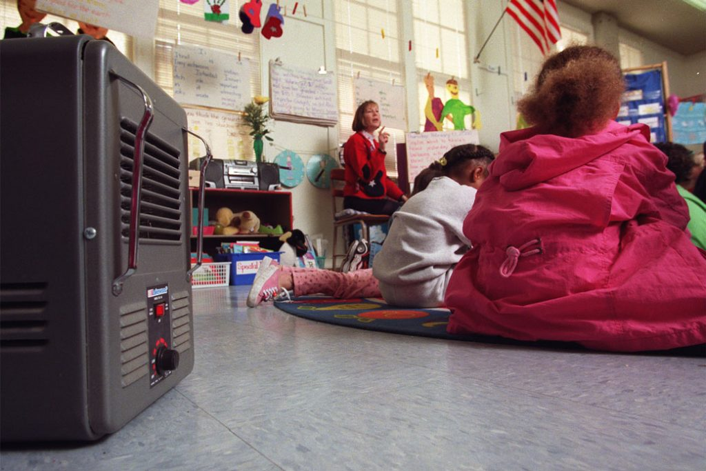 A kindergarten teacher in Los Angeles uses an electric heater for her classroom; the school's air conditioning and heating system has been out of service for more than a year.
