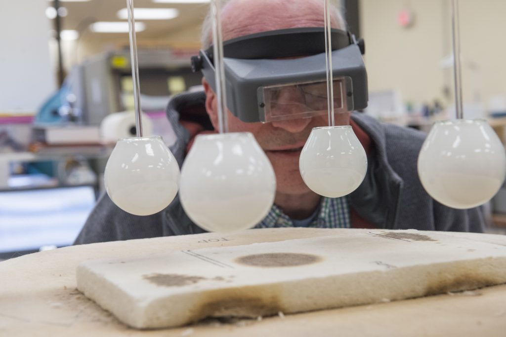 """A man oversees the bake-out process on a new """"acandescent"""" lightbulb in Woburn, Massachusetts, March 2014."""