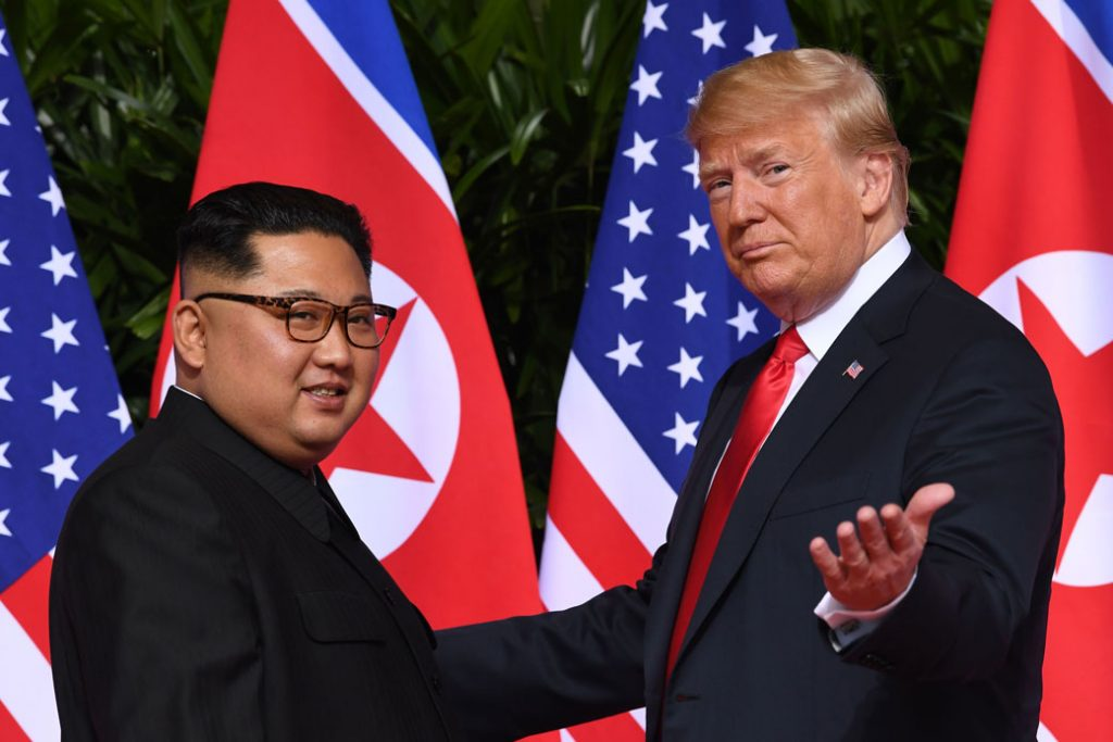 U.S. President Donald Trump gestures as he meets with North Korean leader Kim Jong Un at the start of their historic summit in Singapore on June 12, 2018.