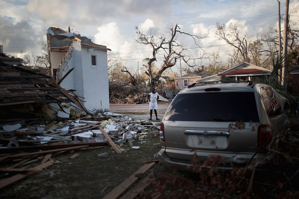 A woman stands between her home and the church next door, both of which were severely damaged by Hurricane Michael on October 20, 2018, in Panama City, Florida.