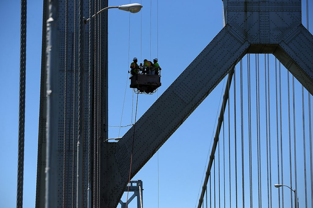 Workers descend from a tower of a San Francisco bridge, August 2013.