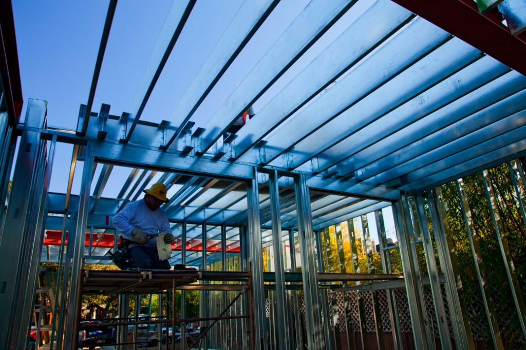 A construction worker assembles steel framing over the foundation of a new, energy-efficient home in Studio City, California, March 2013.