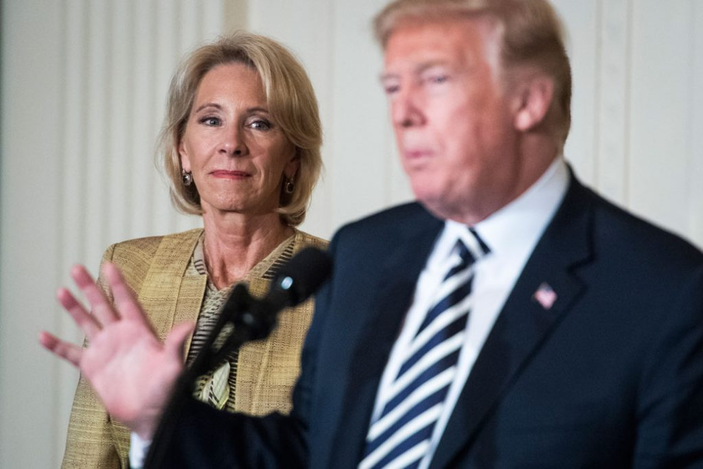 Secretary of Education Betsy DeVos listens as President Donald J. Trump speaks, May 2018.