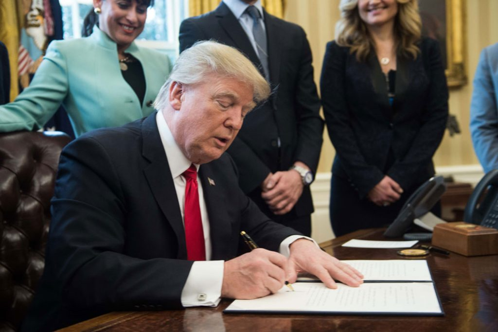 President Donald Trump signs an executive order in the Oval Office at the White House in Washington, D.C., January 2017.