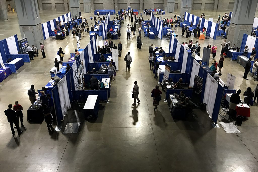 Job seekers mill about employers' booths at a job fair in Washington, D.C., August 2017.