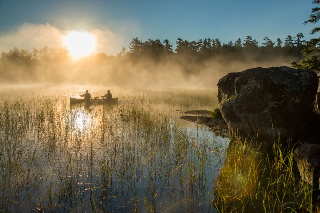 Two canoers paddle through mist in Minnesota's Boundary Waters Canoe Area Wilderness.