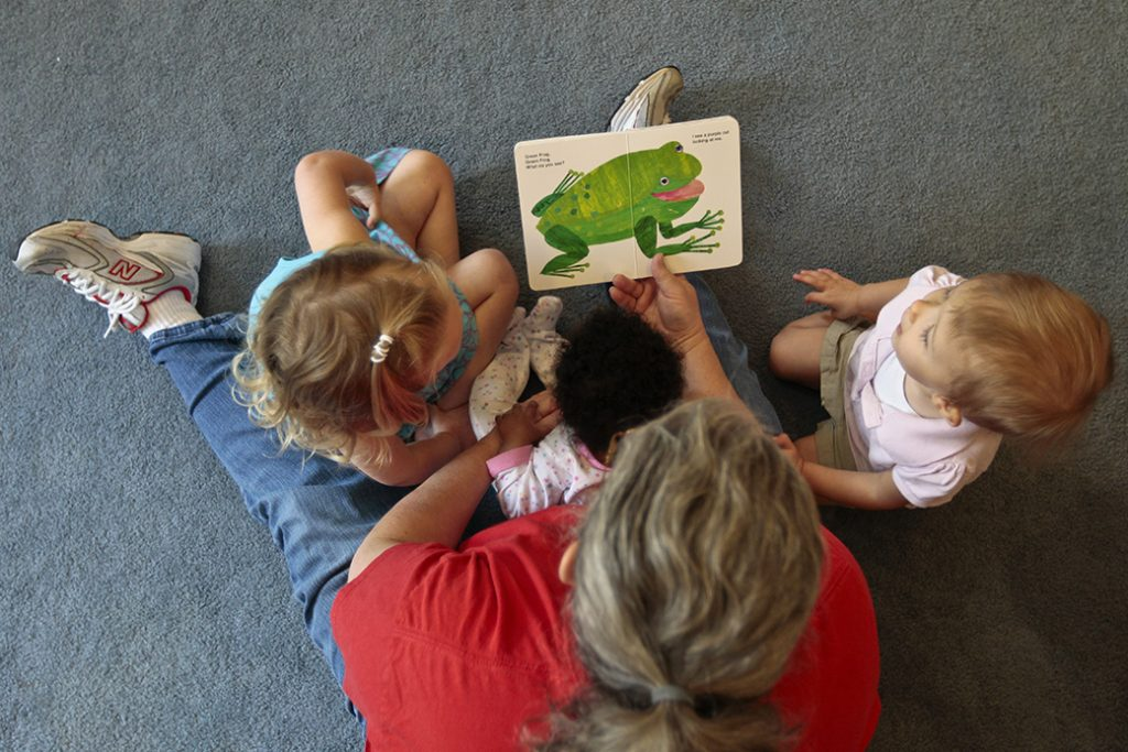 A woman reads to children as she runs her at-home day care in Virginia, July 2012.