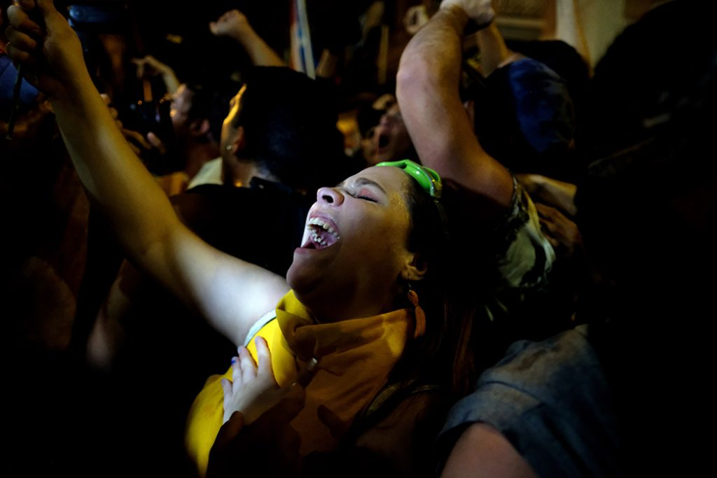 Demonstrators celebrate in front of the Puerto Rican governor's mansion after his resignation message, in San Juan, July 24, 2019.