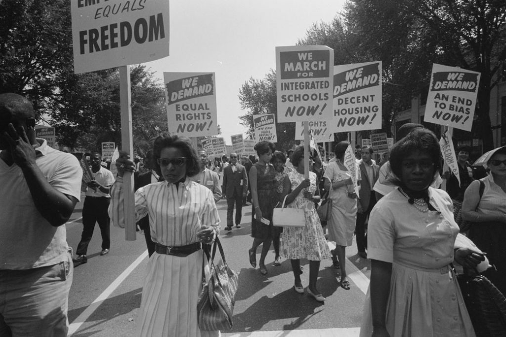 Civil rights advocates carry placards during the March on Washington for Jobs and Freedom on August 28, 1963, in Washington, D.C.
