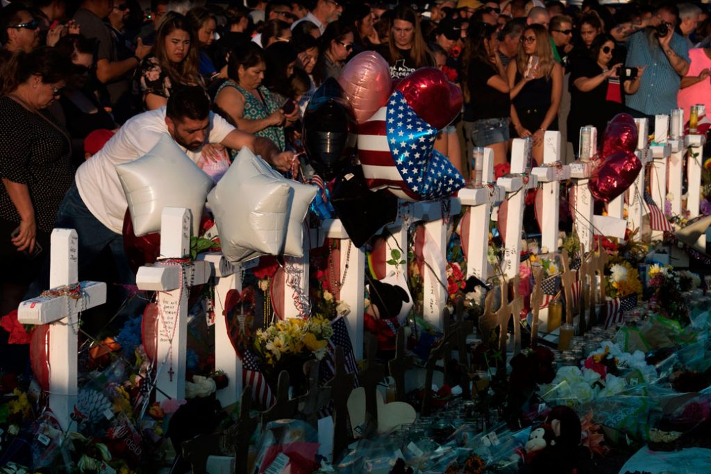 People pay their respects at the makeshift memorial for victims of the shooting that left a total of 22 people dead in El Paso, August 2019.