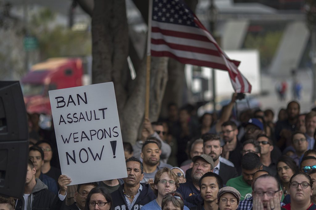 A sign calling for a ban on assault weapons is held at a vigil in Los Angeles for the Pulse nightclub shooting, June 2016.