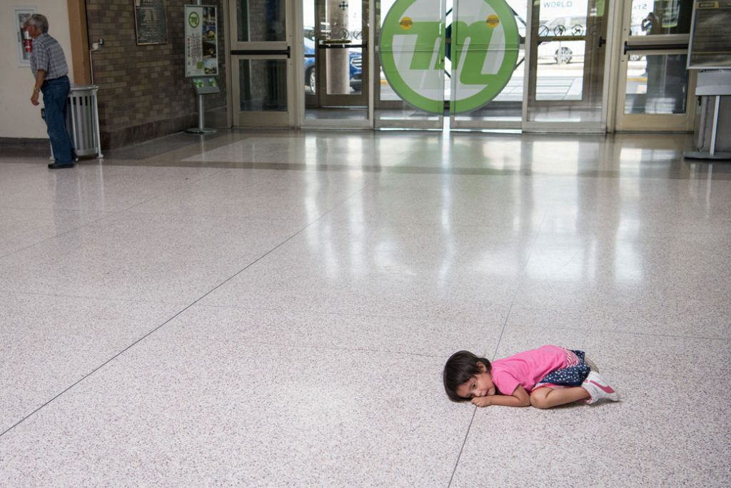 A young migrant girl lies on the floor of a bus depot as her father, recently released from federal detention with other Central American asylum-seekers, obtains a ticket in McAllen, Texas, June 2019.