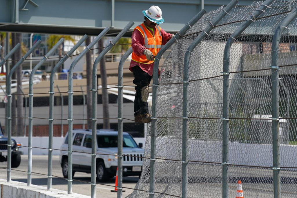 A worker takes down a chain-link fence in Long Beach, California, April 2019.