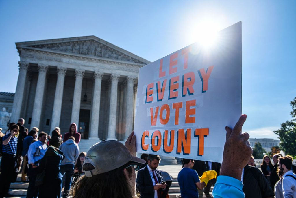 "People hold signs during a rally at the U.S. Supreme Court in Washington, D.C., calling for ""an end to partisan gerrymandering,"" October 3, 2017."