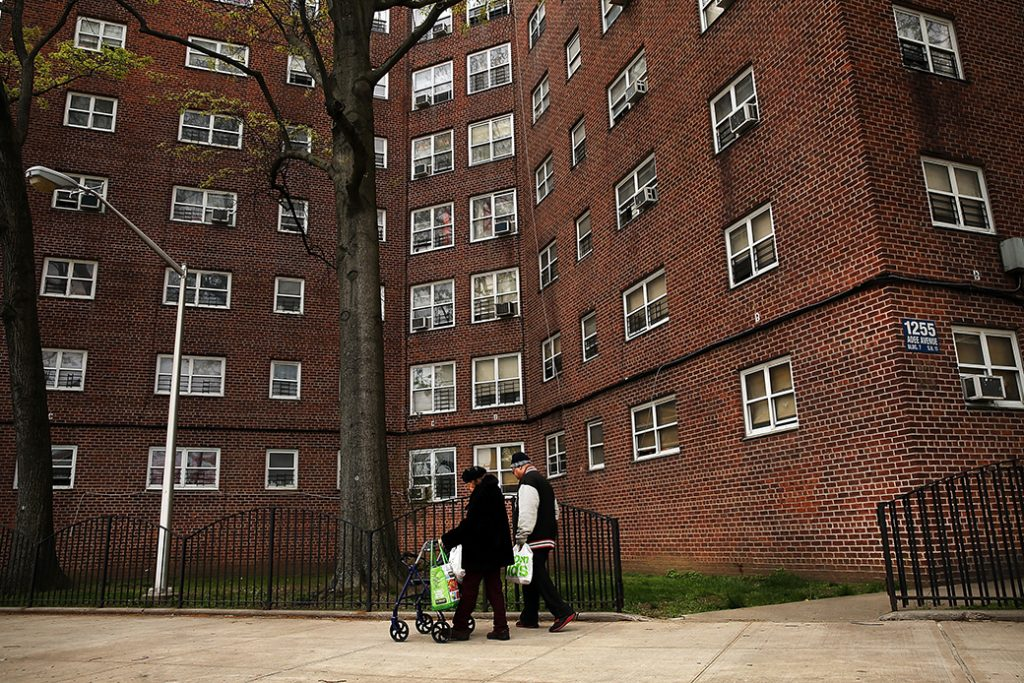 Residents walk through a housing complex in the Bronx, April 2016, in New York.