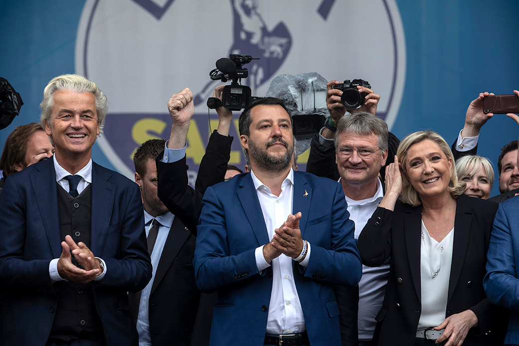 Four leaders of right-wing European populist parties (Geert Wilders of the Netherlands, Matteo Salvini of Italy, Jörg Meuthen of Germany, and Marine Le Pen of France) are pictured clapping and smiling at a rally.