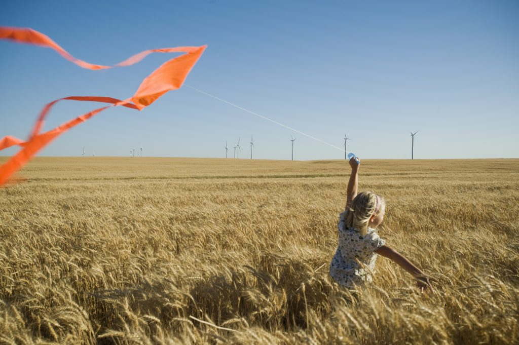A girl runs with a kite on a wind farm.