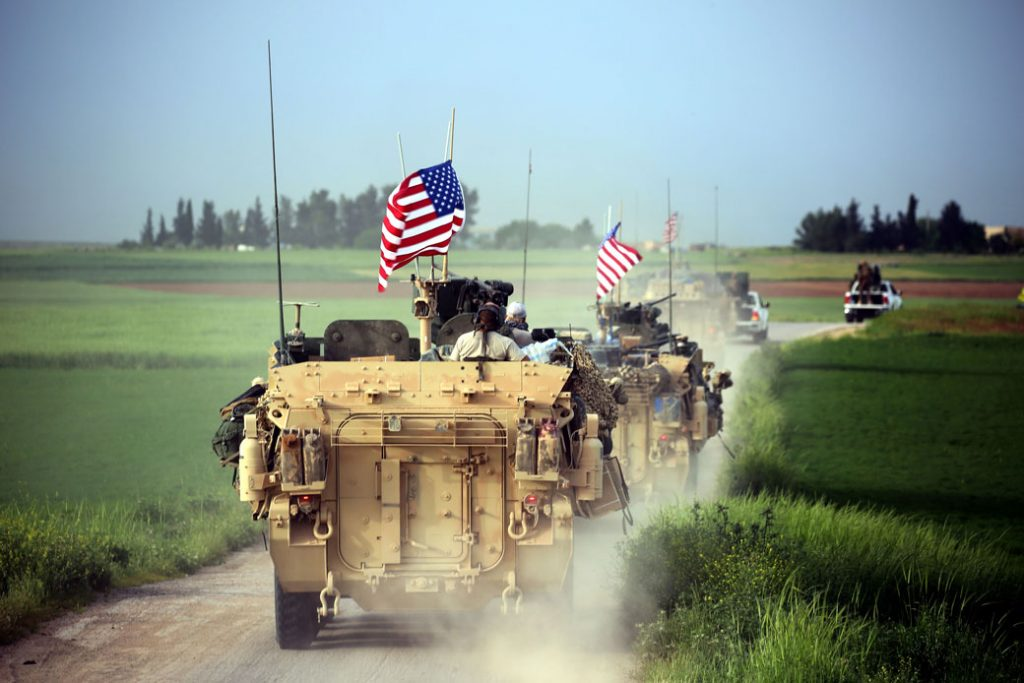 U.S. forces, accompanied by Kurdish YPG fighters, drive armored vehicles near the northern Syrian village of Darbasiyah in April 2017.
