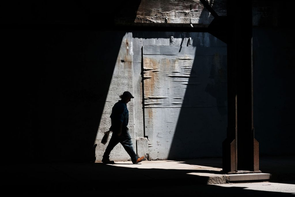 A man walks along a street in Lawrence, Massachusetts, which has struggled to find its economic base since the decline of manufacturing, August 2019.