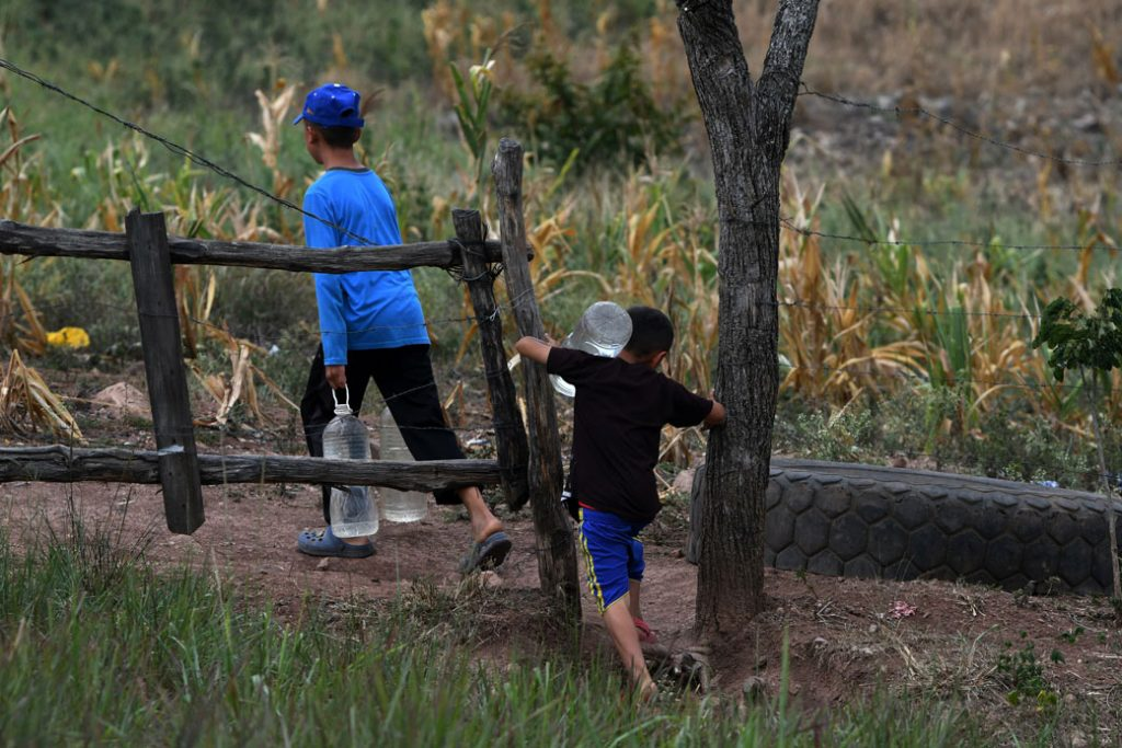 Children carry bottles of water near Los Laureles reservoir, close to the Honduran capital of Tegucigalpa, during a drought caused by climate change.