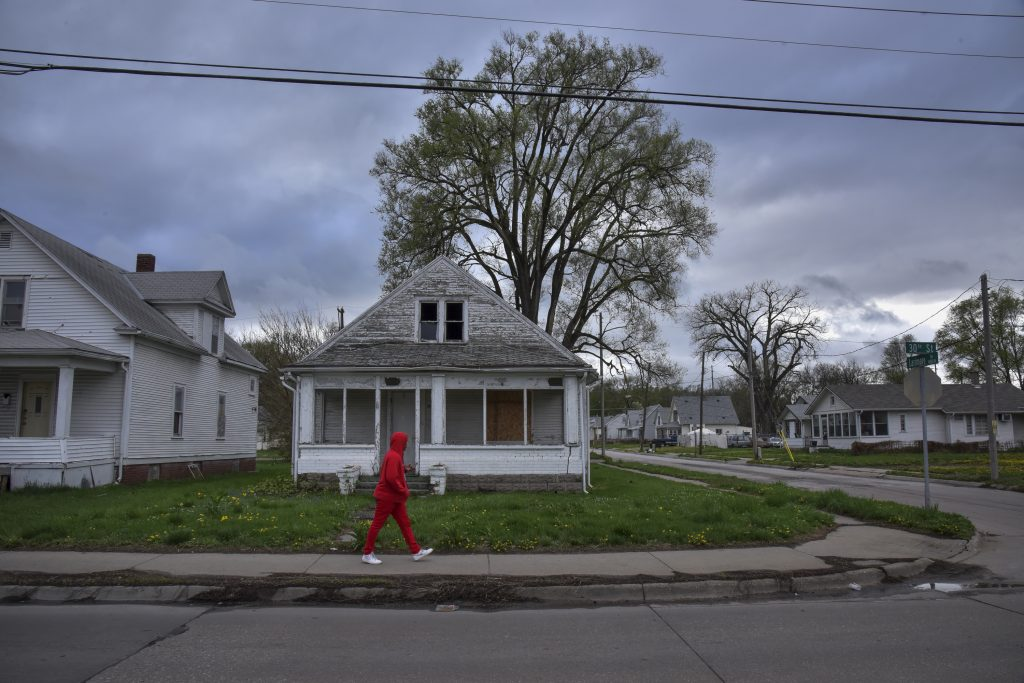A pedestrian passes in front of a shuttered house in Omaha, Nebraska on a cloudy evening on Thursday, May 3, 2018.