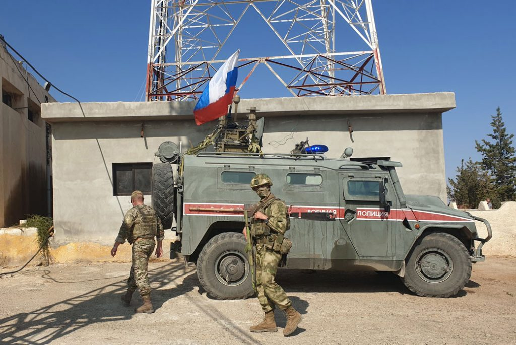 Russian soldiers walk past a Russian military police armoured vehicle at a position in the northeastern Syrian city Kobani, October 2019.