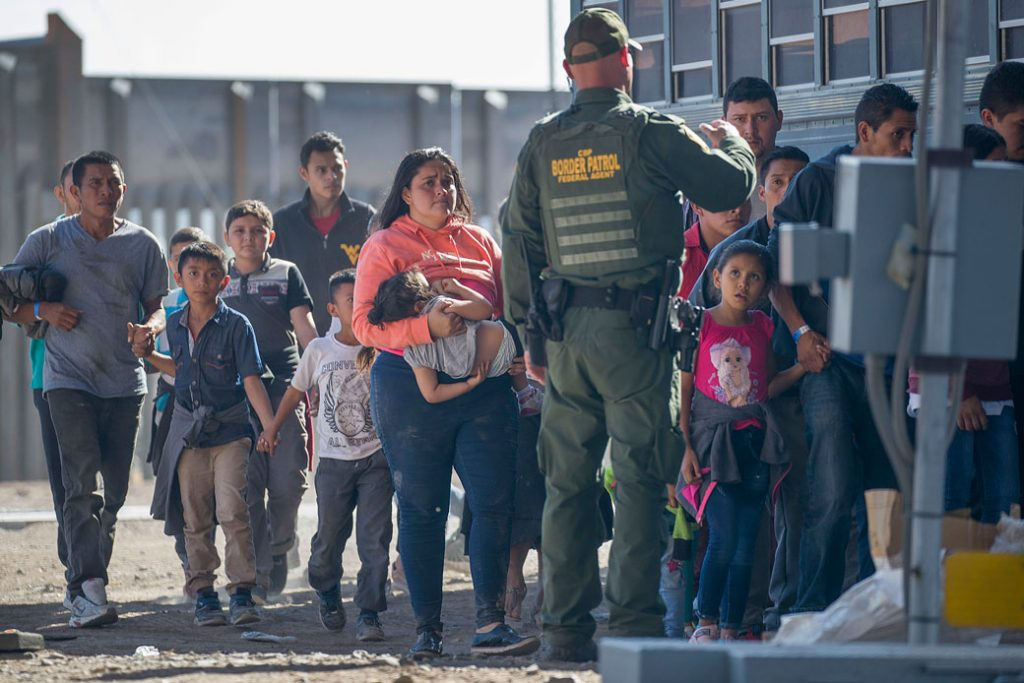 A U.S. Border Patrol agent in El Paso, Texas, directs a group of migrants on to a bus, June 2019