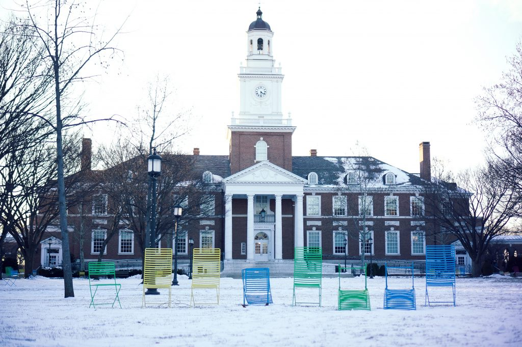 Several multicolored lawn chairs are lined up in front of Gilman Hall on the snowy Keyser quadrangle on the Homewood campus of the Johns Hopkins University in Baltimore, Maryland, January 2015.