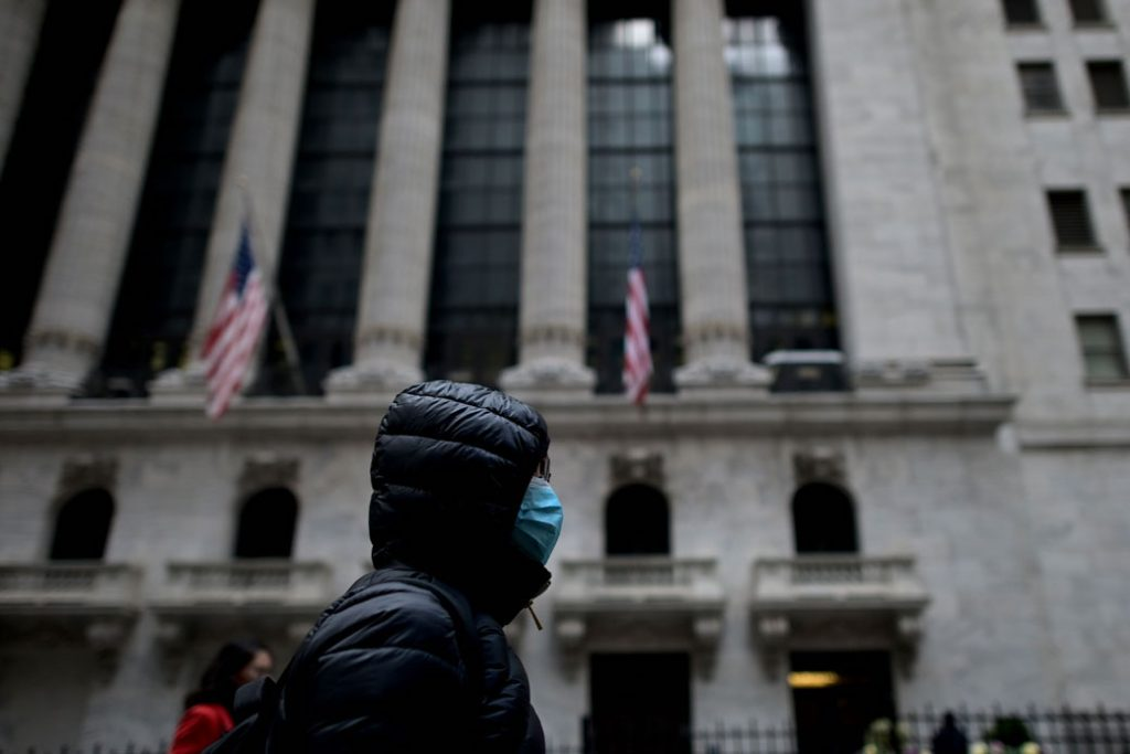 A woman wearing a face mask passes by the New York Stock Exchange in New York City, February 3, 2020.
