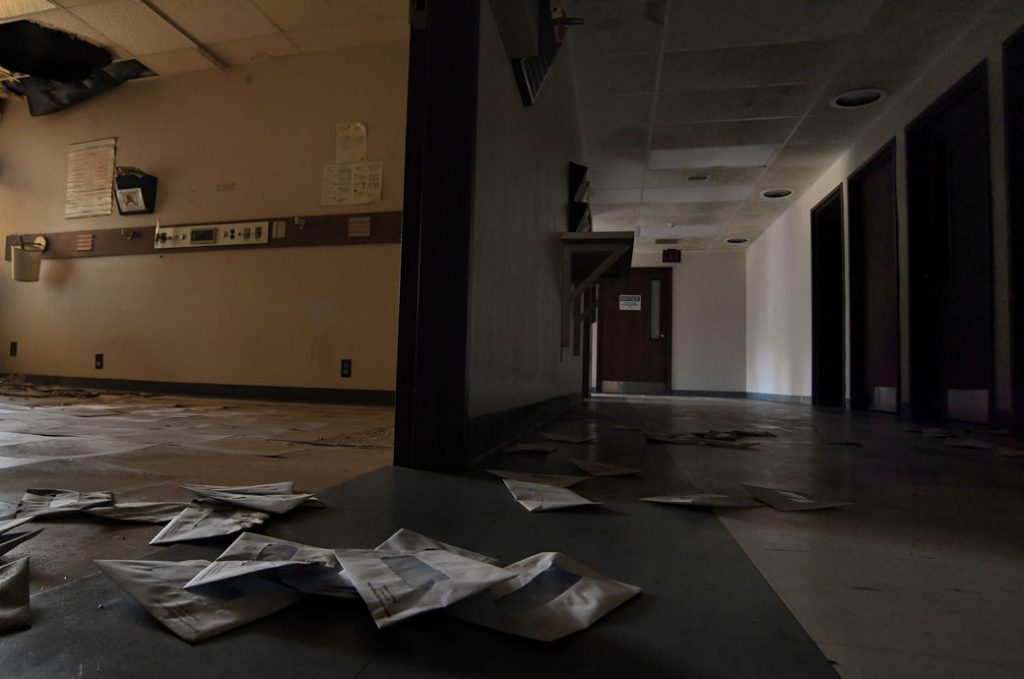Billing envelopes litter the floor of the shuttered Southeast Health Center in Ellington, Missouri, July 2019.