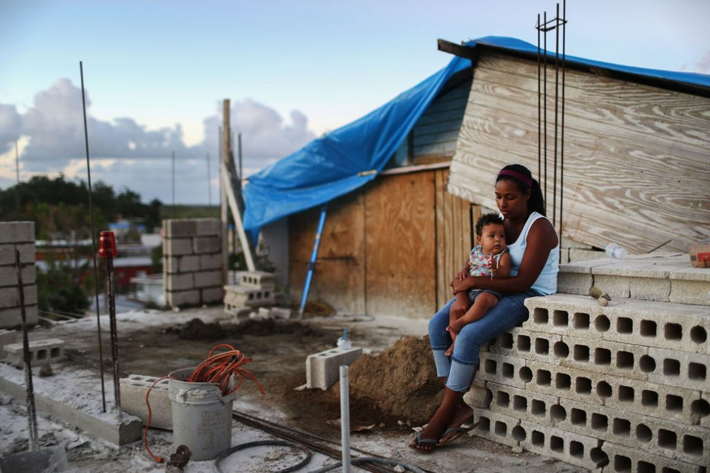 A mother holds her baby at their home, which is under construction after being mostly destroyed by Hurricane Maria, in San Isidro, Puerto Rico, December 2017.