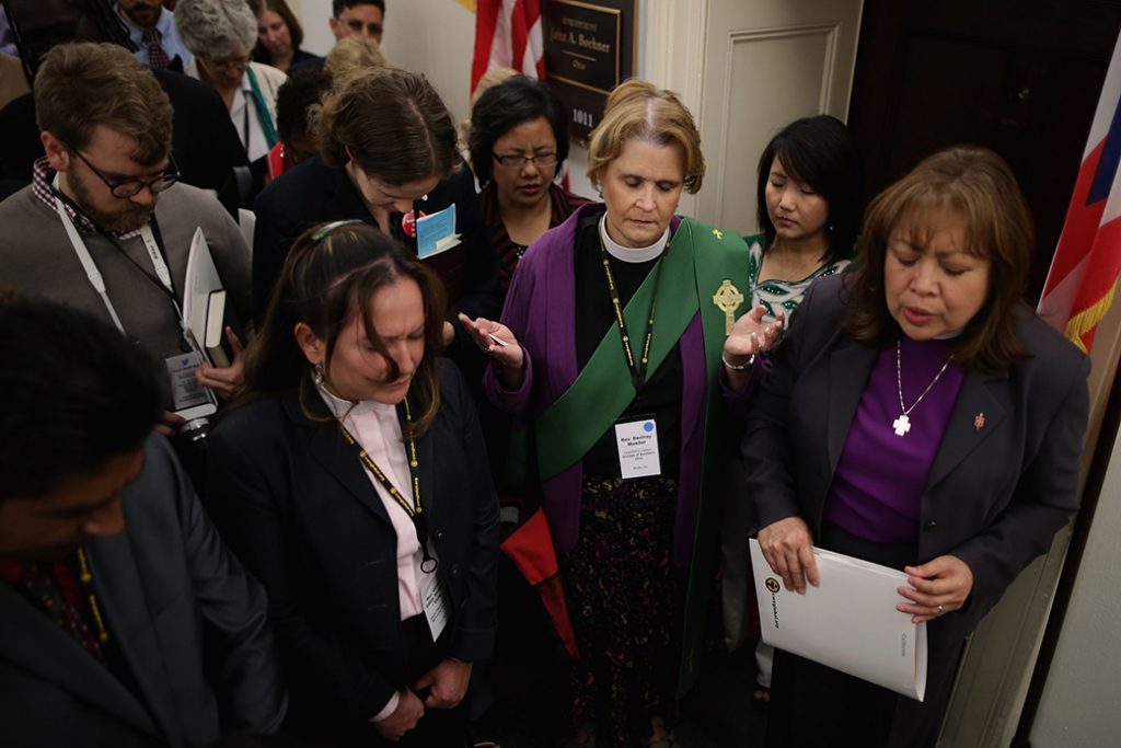 Bishop Minerva Carcaño (R) and other faith leaders and lay people join in prayer outside the constituent office of then-Speaker of the House John Boehner (R-OH) while lobbying for immigration reform, October 8, 2013, in Washington, D.C.