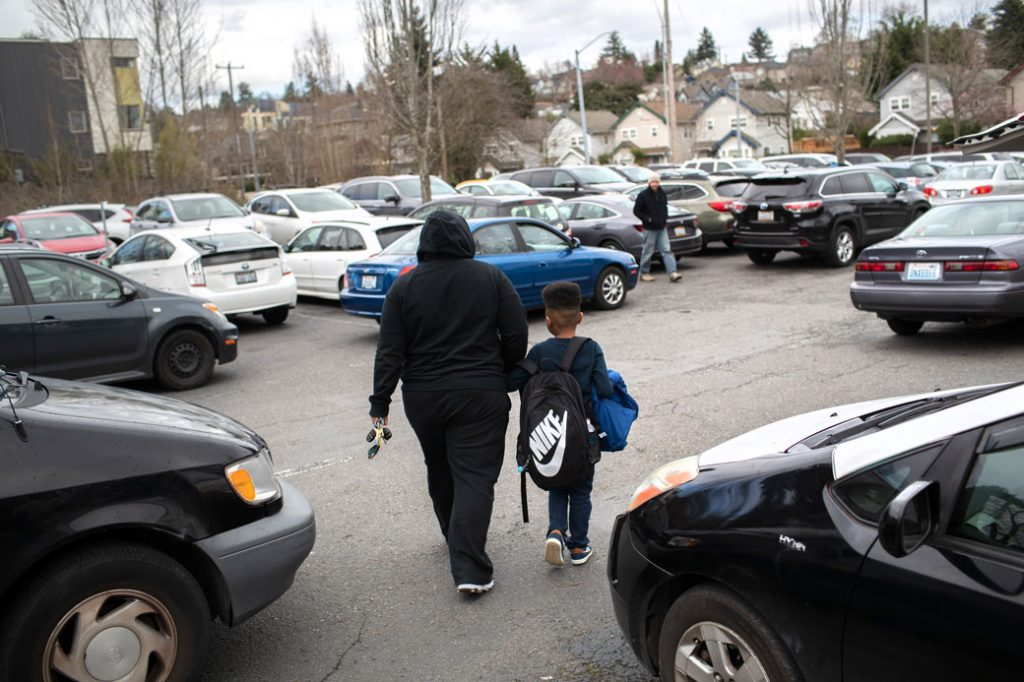 A student leaves elementary school with a parent after the Seattle Public School system was closed abruptly due to coronavirus fears on March 11, 2020.