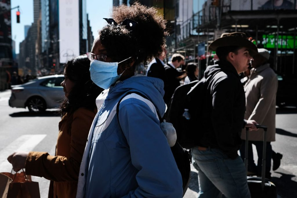 People walk through Manhattan with surgical masks as fears of the novel coronavirus outbreak increase in the United States, March 2020.