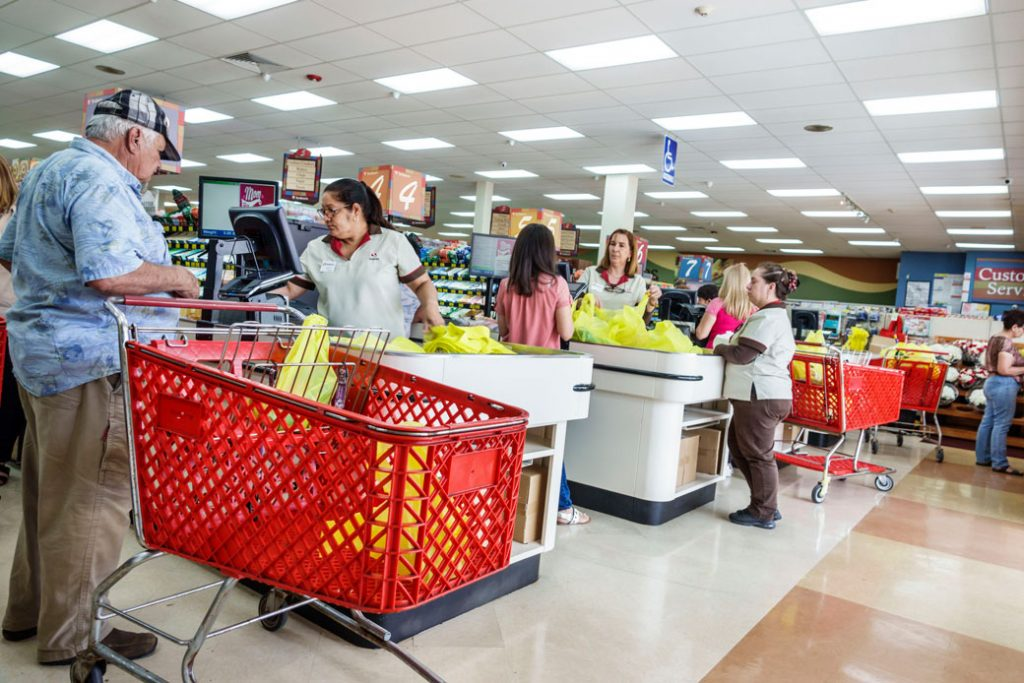 Store employees check out customers at a supermarket in Miami, May 2018.