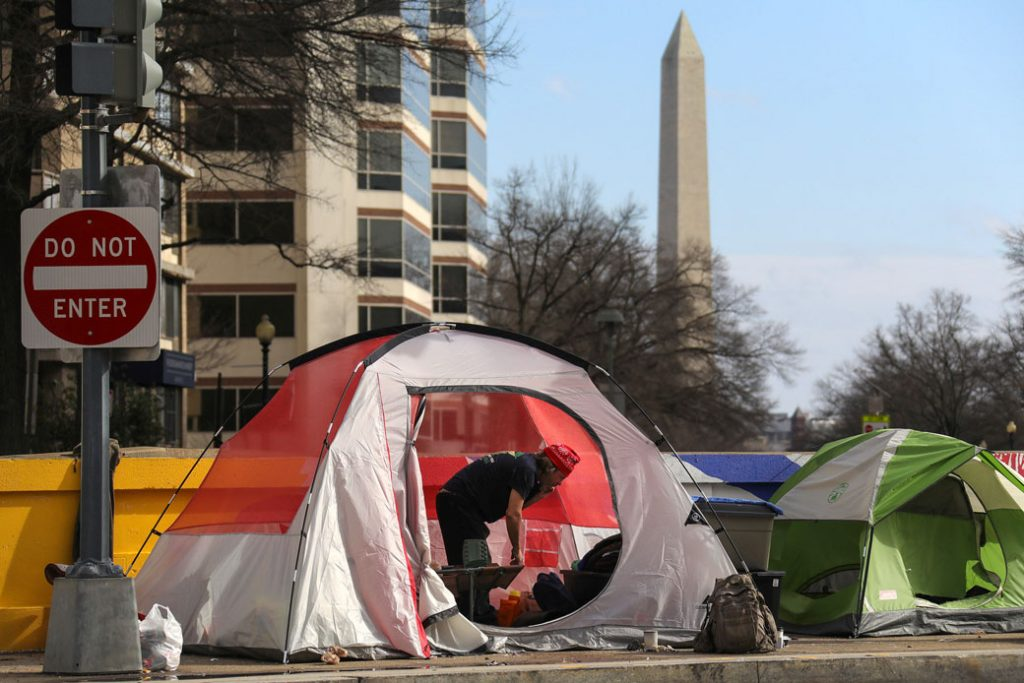 A man in a tent stands among other shelters belonging to people experiencing homelessness in Washington, D.C., February 2020.