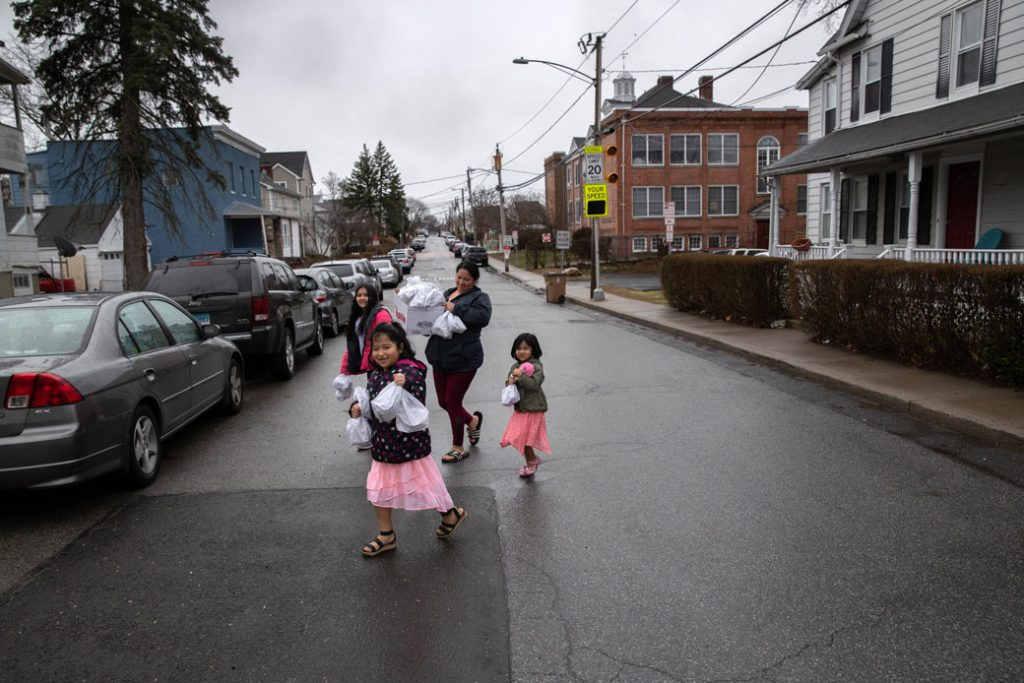 Families in Stamford, Connecticut, carry home free bagged meals given out as part of the city's response to the COVID-19 pandemic, March 2020.