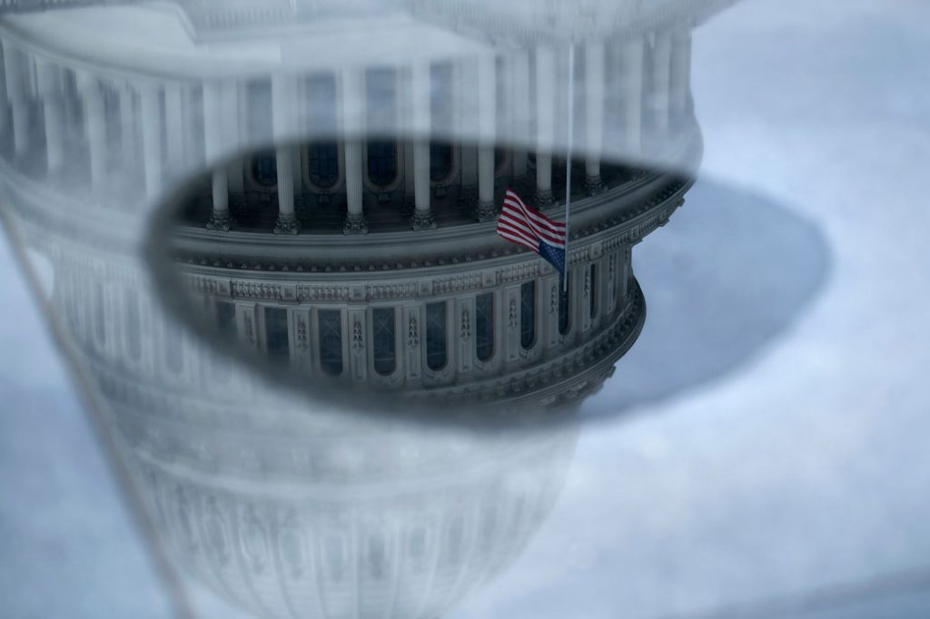 The U.S. Capitol is reflected in water as negotiations on a COVID-19 economic bailout continue on March 24, 2020, in Washington, D.C.
