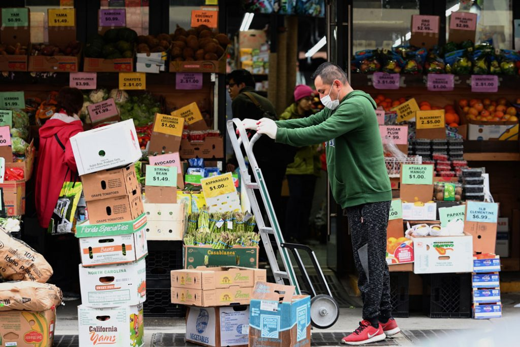 A worker stocks groceries at a local supermarket in Brooklyn, New York, on March 20, 2020.