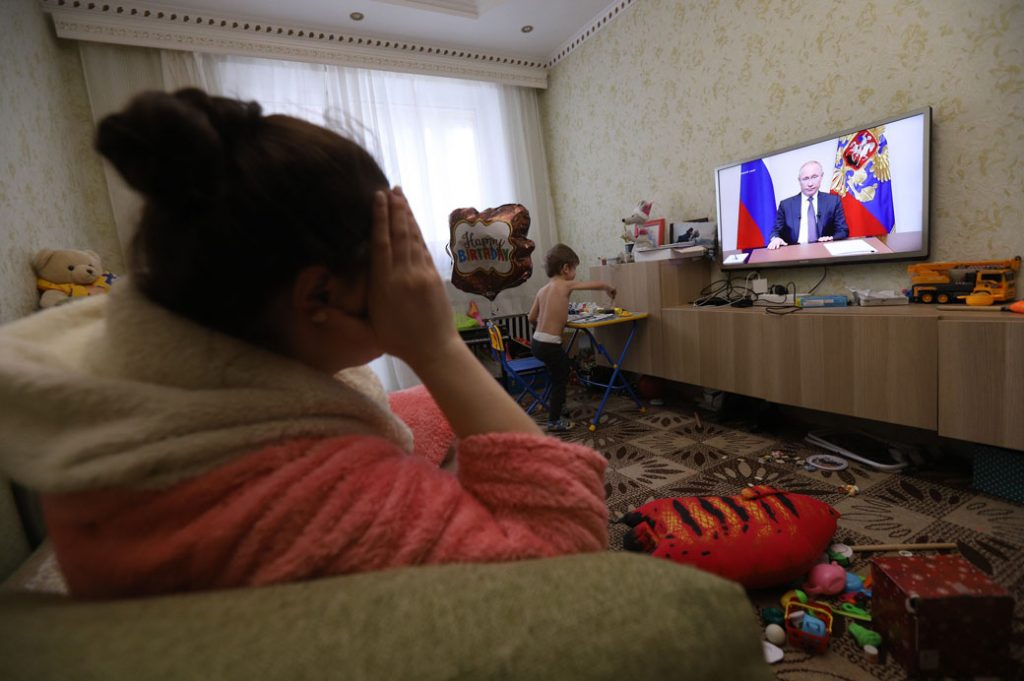A woman watches Russian President Vladimir Putin addressing the nation about the coronavirus pandemic, March 25, 2020.
