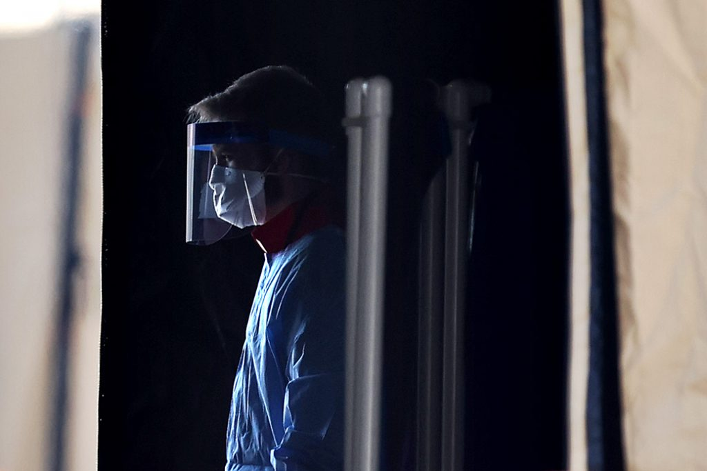A health care professional prepares to screen people for the coronavirus at a testing site erected by the Maryland National Guard in a parking lot in Landover, Maryland, March 30, 2020.