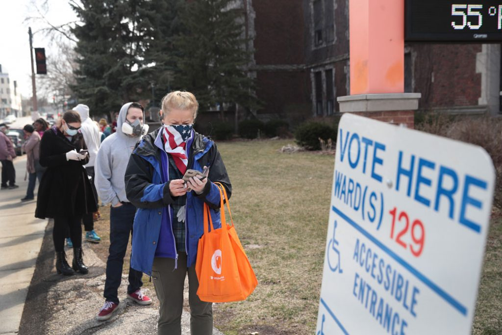 Voters wait in line to enter a polling location in Milwaukee on April 7, 2020.