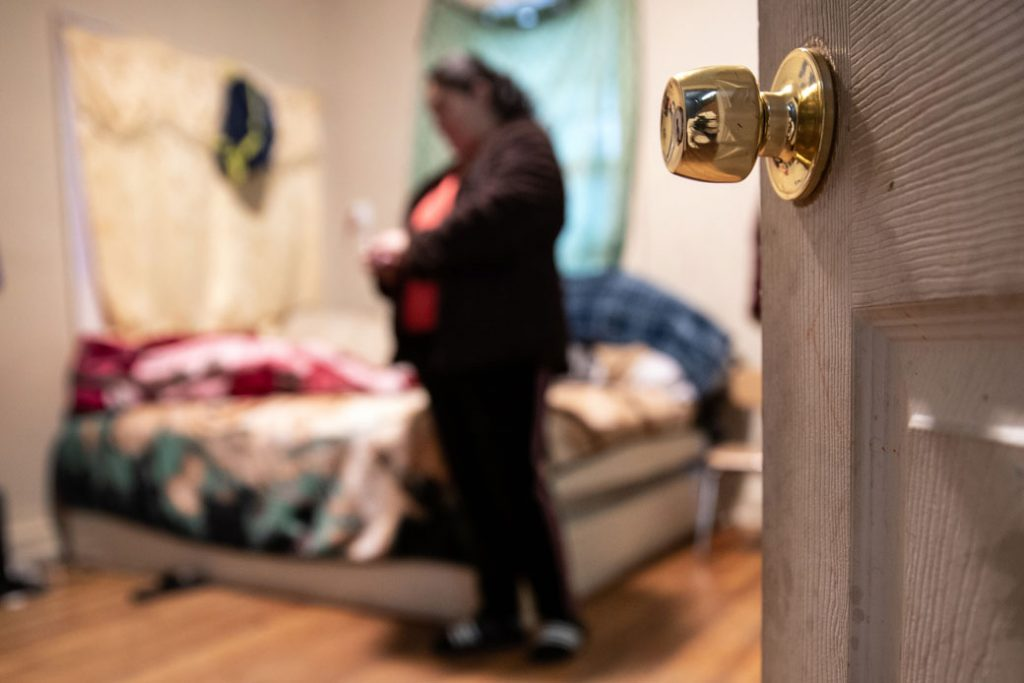 A woman stands in her bedroom while self-quarantining in a Long Island rental house with her family, March 2020.
