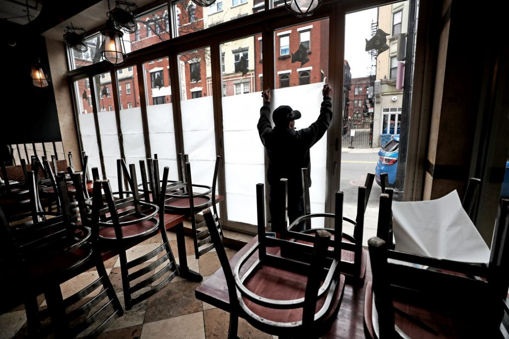 An employee at a Boston restaurant tapes paper in the windows following a statewide order to close all nonessential businesses in Massachusetts during the COVID-19 pandemic, March 2020.