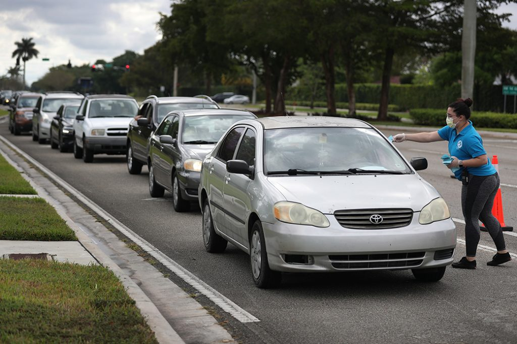 A woman gives vouchers for groceries, provided by the food bank Feeding South Florida, to people lined up in their vehicles on April 6, 2020, in Sunrise, Florida.