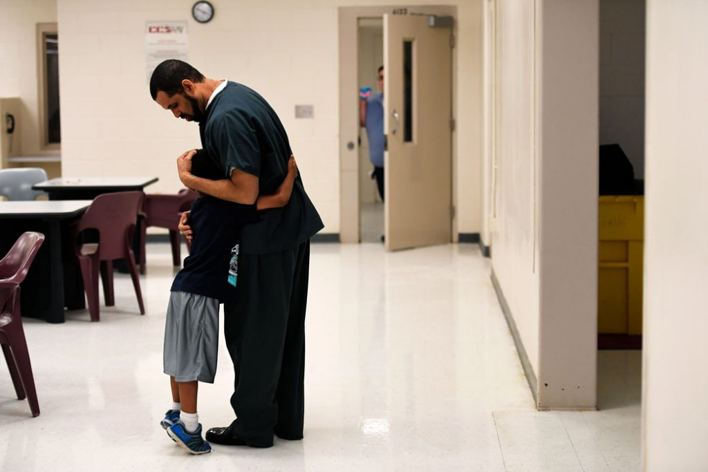 A 6-year-old boy hugs his father, an inmate at a correctional center in Burlington, Colorado, June 2016.