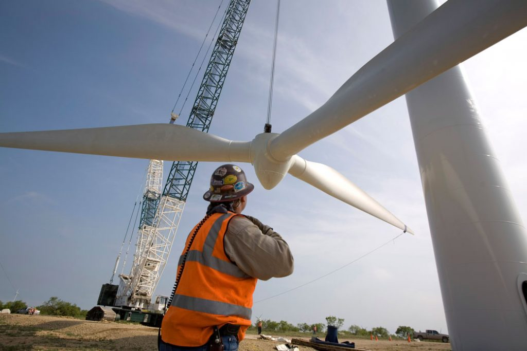 A crane slowly lifts a rotor onto a tower at a wind farm north of Abilene, Texas, June 2007.